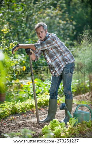 Portrait of a man with a spade exhausted by gardening - stock photo
