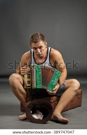 Portrait of a man with accordion sitting on retro suitcase and begging with hat - stock photo