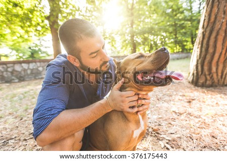Portrait of a man with dog at park. He is looking at his dog standing with open mouth. The main subject is the dog, the man is standing behind it. - stock photo