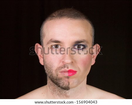 Portrait of a man with half face makeup as a woman and isolated on black background. - stock photo