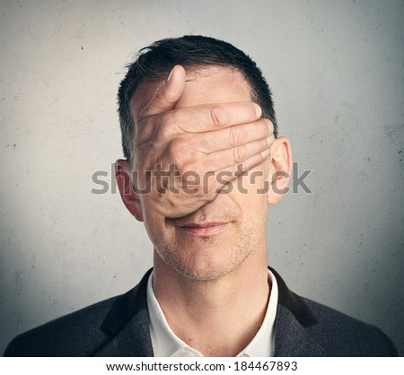 Portrait of a man with hand closing his eyes - stock photo