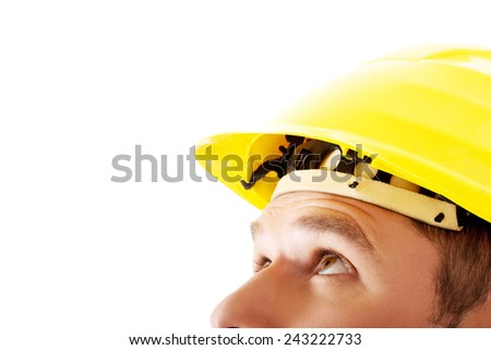 Portrait of a man with hardhat looking up. - stock photo