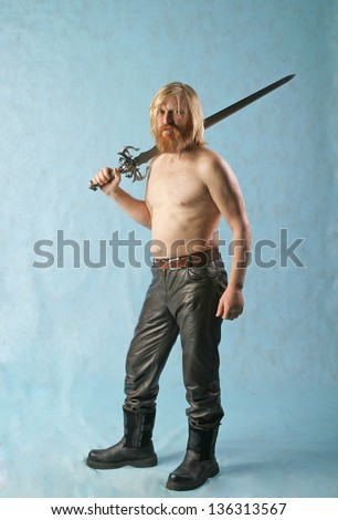 portrait of a man with long hair, beard and mustache with a sword on a light background in full length - stock photo