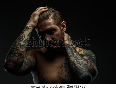 Portrait of a man with naked torso and tattooes. Dark and deep shadows.  - stock photo
