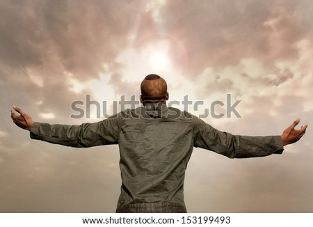 Portrait of a man with outstretched arms looking at the sky - stock photo