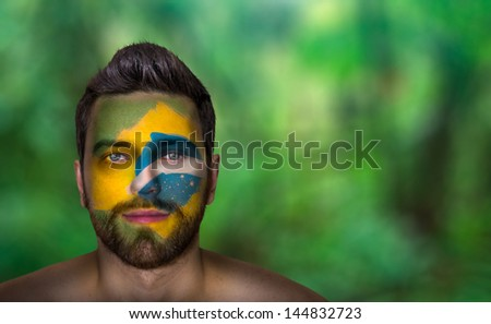 Portrait of a man with the flag of the Brazil painted on his face - stock photo