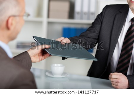 Portrait of a manager giving folder to a male applicant in his office - stock photo