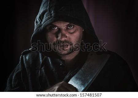 portrait of a maniac killer with a hatchet - stock photo