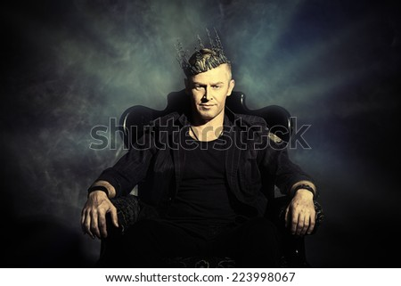 Portrait of a masculine handsome man in elegant black suit sitting in a chair in a classic vintage style.  - stock photo
