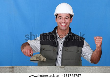 Portrait of a mason busy constructing a wall - stock photo