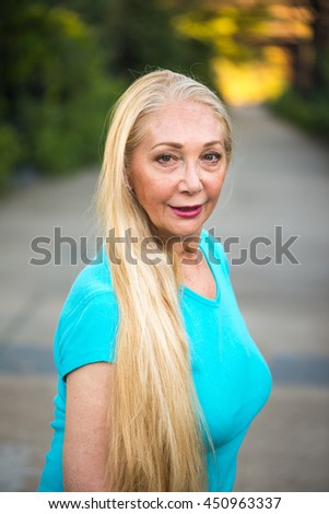 Portrait of a mature blonde woman with long blonde hair on a bridge  - stock photo