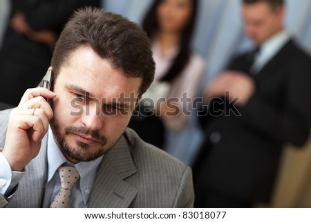Portrait of a mature business man on phone in office environment - stock photo
