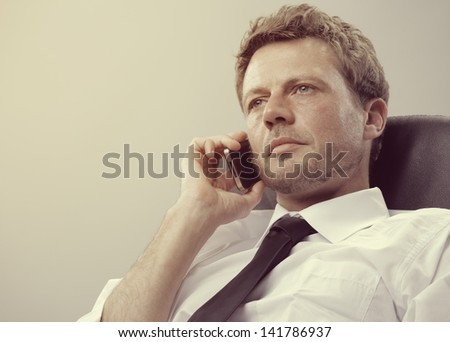 Portrait of a mature business man talking on phone - stock photo
