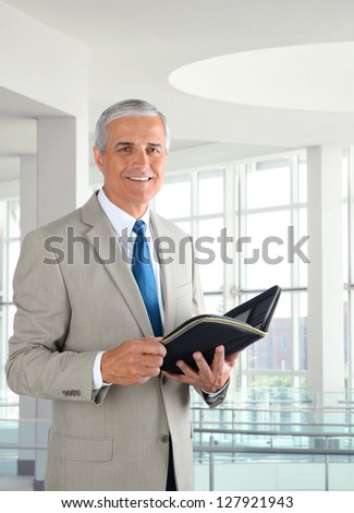 Portrait of a mature businessman standing in a modern office. Man is holding a small binder and smiling at the camera. - stock photo