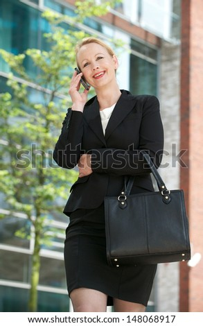 Portrait of a mature businesswoman calling by mobile phone in the city - stock photo