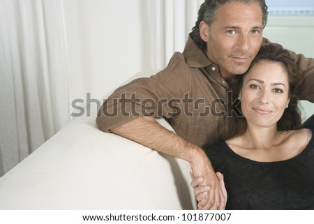 Portrait of a mature couple lounging on a sofa at home and holding hands. - stock photo