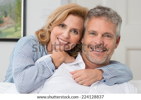 Portrait Of A Mature Couple Smiling And Embracing At Home - stock photo