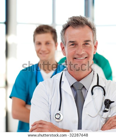 Portrait of a mature doctor leading his team in hospital - stock photo