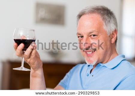 Portrait of a mature man enjoying a glass of red wine at home - stock photo