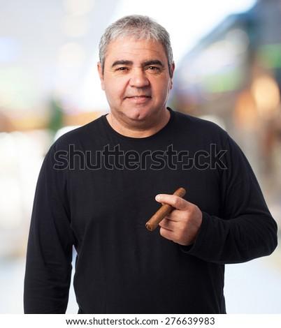 portrait of a mature man smoking a cigar - stock photo