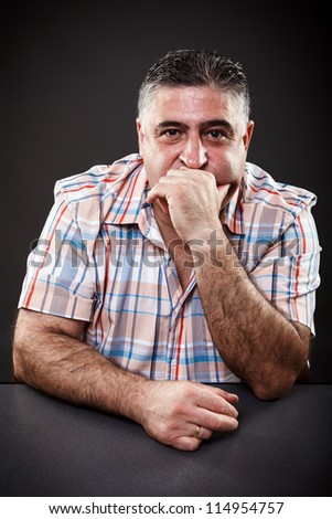 Portrait of a mature man thinking while sitting at table on gray background - stock photo