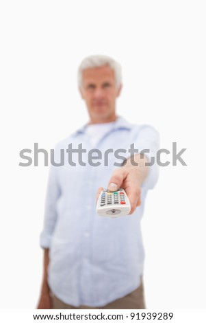 Portrait of a mature man using a remote against a white background - stock photo