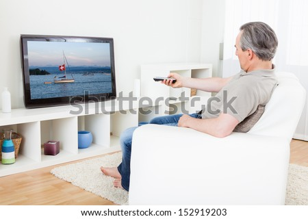 Portrait of a mature man watching tv at home - stock photo