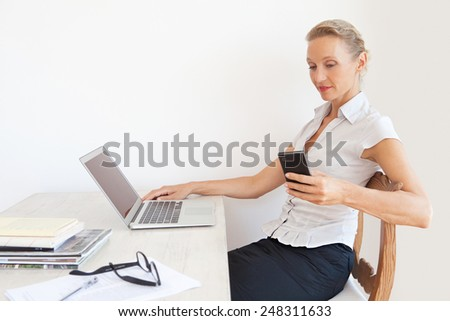 Portrait of a mature professional woman holding a smart phone device and using a laptop computer, sitting at her home office with a white wall space, smiling. Business lifestyle technology, interior. - stock photo