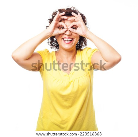 portrait of a mature woman doing a glasses symbol - stock photo