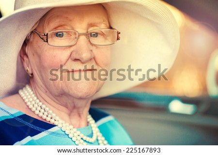 portrait of a mature woman in glasses and hat sitting in car . - stock photo
