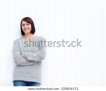 Portrait of a mature woman smiling against white wall - stock photo