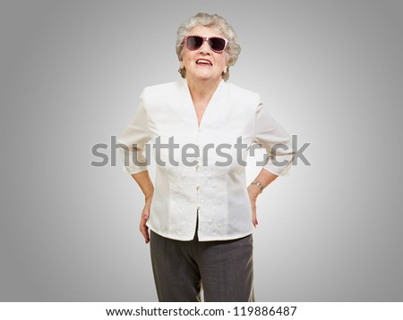 portrait of a mature woman while giving pose on grey background - stock photo