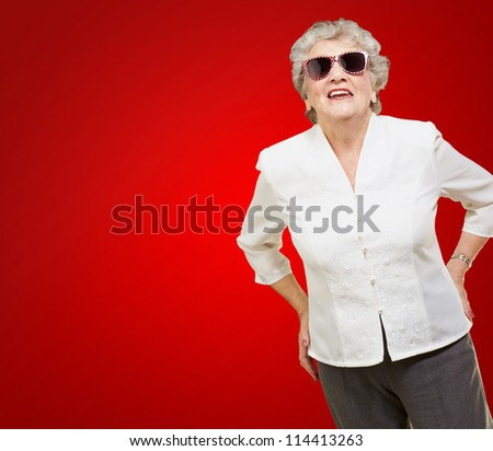 Portrait Of A Mature Woman While Giving Pose On Red Background - stock photo