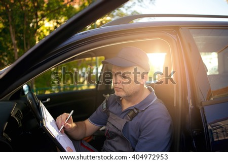 Portrait of a mechanic at work writing on clipboard - stock photo