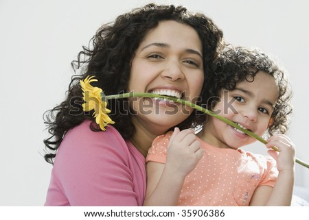 Portrait of a mid adult woman with her daughter holding a flower in their teeth - stock photo
