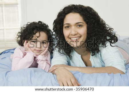 Portrait of a mid adult woman with her daughter lying on the bed - stock photo