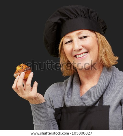 portrait of a middle aged cook woman holding a delicious homemade muffin over a black background - stock photo