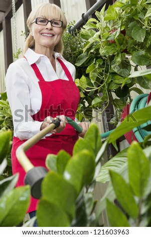 Portrait of a middle-aged female gardener spraying pesticide on plants in botanical garden - stock photo