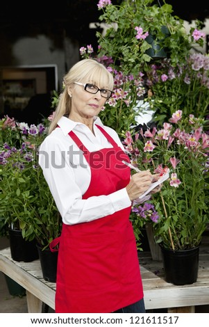 Portrait of a middle-aged florist making notes in garden center - stock photo