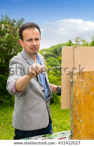 Portrait of a middle-aged male artist in the process of painting his picture outdoors with background of beautiful trees - stock photo