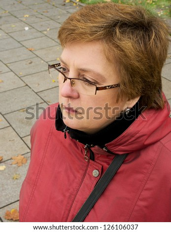 Portrait of a middle-aged woman in a red jacket and glasses - stock photo