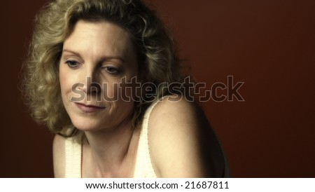 Portrait of a middle aged woman sitting in a chair and looking sad - stock photo