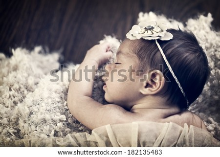 Portrait of a mixed race 6 week old newborn baby girl asleep in blankets with vintage filtered effect - stock photo