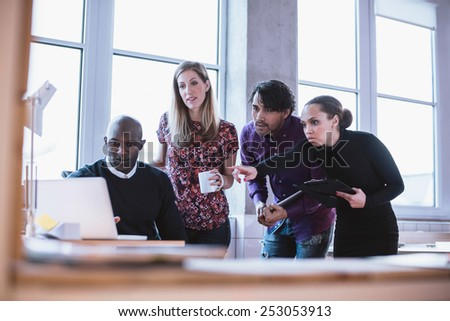 Portrait of a modern business team working at new project during meeting and looking at laptop. Multiracial business people working together. - stock photo