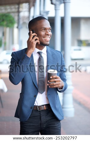Portrait of a modern businessman walking and talking on mobile phone - stock photo