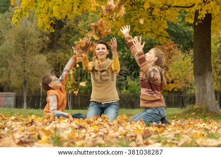 Portrait of a mom with kids in autumn park - stock photo