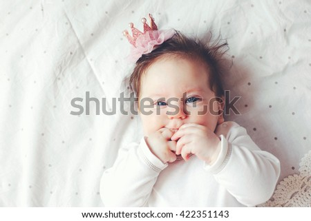 Portrait of a 4 month cute baby girl wearing princess crown headband and lying down on a bed with polka dot white bedding, top view - stock photo