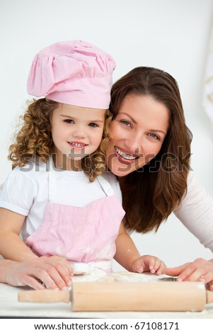 Portrait of a mother and daughter at a table in the kitchen - stock photo