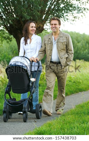 Portrait of a mother and father walking outdoors with baby stroller - stock photo