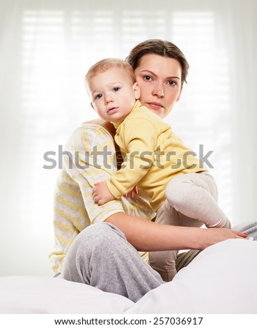 Portrait of a mother and her baby daughter on light window background - stock photo